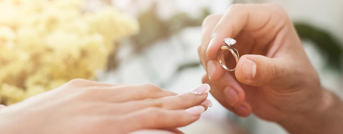 Mann steckt Frau Verlobungsring an Finger