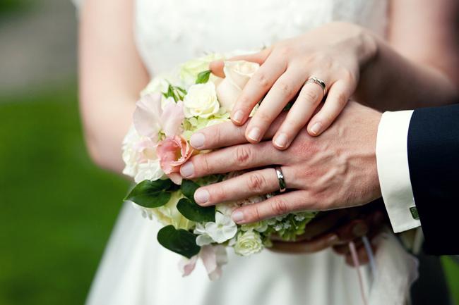 Brautpaar mit Strauss und Eheringen an den Händen in Stuttgart